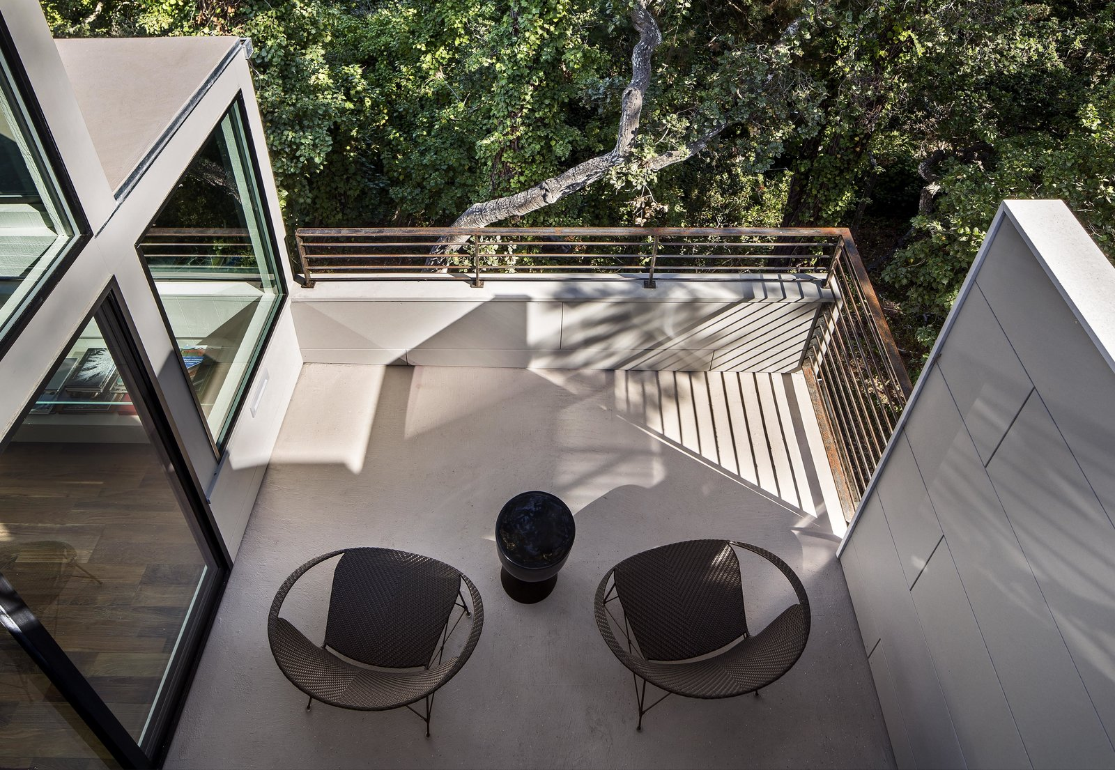 """When you have a tiny house, having outdoor spaces off a room can make a big difference,"" Schicketanz says. Luckily, each room already had its own deck, which the architect simply refurbished by installing concrete floors and galvanized stainless steel railings."