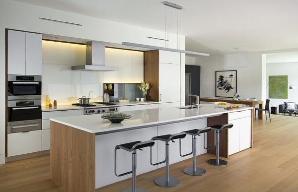 The kitchen features a Henrybuilt kitchen system and quartz countertops. The refrigerator is Sub-Zero, the range is Wolf, and the wall ovens and warming drawer are Miele.