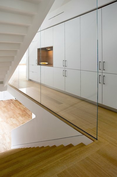 A custom staircase with wood risers is encased by glass panels. A wall of Henrybuilt's kitchen system adds storage to the hallway.