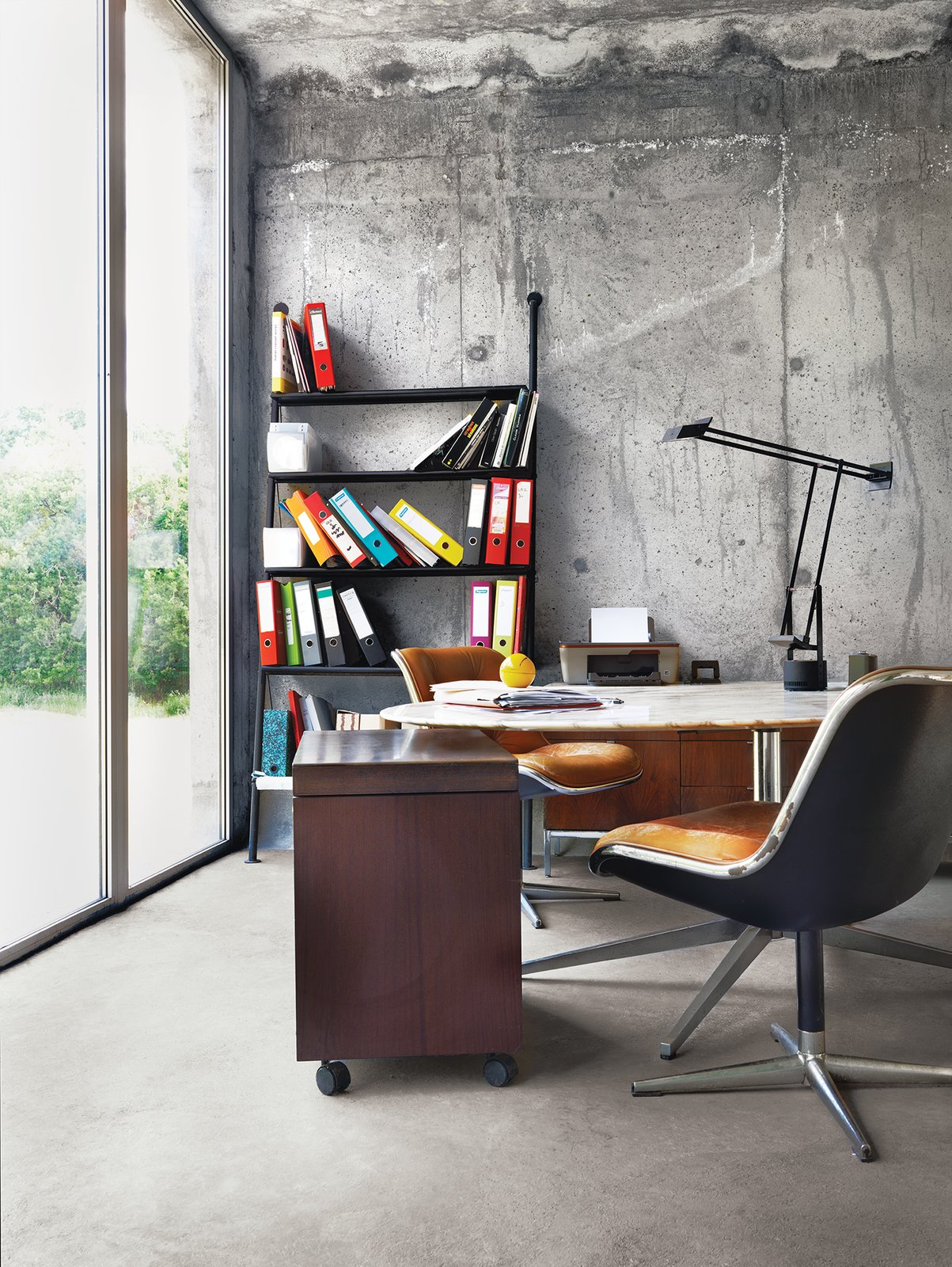 Outfitted with Pollock desk chairs and a marble-topped conference table by Knoll, the office in Monory's French farmhouse pays homage to international design. The Tizio task lamp is by Richard Sapper for Artemide, and the leaning John Ild bookshelf was designed by Philippe Starck for Disform in 1977.  Photo 9 of 12 in Matali Crasset Renovates Monory Farmhouse