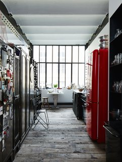 10 Dreamy Parisian Homes - Photo 9 of 10 - A Smeg refrigerator is one of a series of red accents that punctuate the black-and-white space.