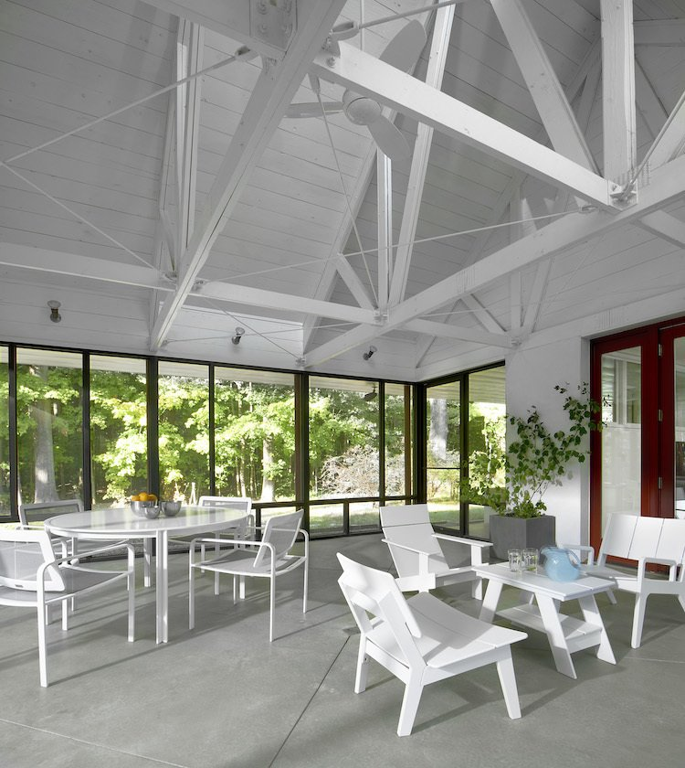 The 400-square-foot porch, a central focus of the home, was wrapped in a Kawneer window framing and screen—probably the biggest material indulgence. A south-facing skylight above the porch draws in air and ventilates the entire cottage, dropping temperatures about 10 degrees. The table-and-chair set on the left is by Brown Jordan, while the coffee table and chairs are from Sojourn in Sawyer, Michigan.  Photo 6 of 8 in Modern Cottage Renovation in Michigan