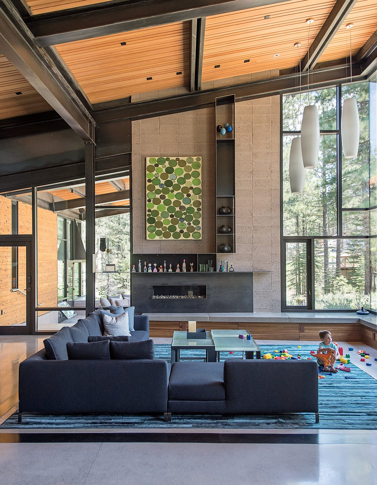 A piece by John Belingheri hangs in the living room of the Bancroft family's home, which is centered by an Antonio Citterio sofa and Robert Marinelli tables.  Photo 1 of 19 in A Forest Sanctuary Designed to Support Autistic Triplets, Their Parents, and a Host of Caregivers
