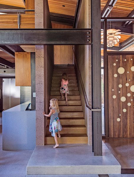 The entrance is highlighted by a custom walnut door designed by the architect, Jack Hawkins. Cheryl Chenault designed the interiors.  Photo 2 of 19 in A Forest Sanctuary Designed to Support Autistic Triplets, Their Parents, and a Host of Caregivers