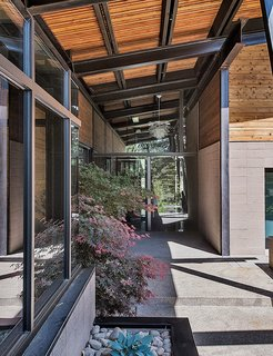 The entrance introduces the home's main materials: steel, glass, wood, and concrete.