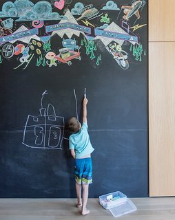 A Forest Sanctuary Designed to Support Autistic Triplets, Their Parents, and a Host of Caregivers - Photo 5 of 19 - The library holds a wall-size blackboard for the Bancrofts' four children, with a colorful permanent piece by local artist Derek Phillips.