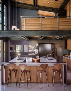 A Forest Sanctuary Designed to Support Autistic Triplets, Their Parents, and a Host of Caregivers - Photo 8 of 19 - Norman Cherner barstools from Design Within Reach line the island in the kitchen, which is crowned by an open loft office. The faucets are from Dornbracht; the countertops are Caesarstone. Hawkins integrated a steel-clad casual eating nook, at left.