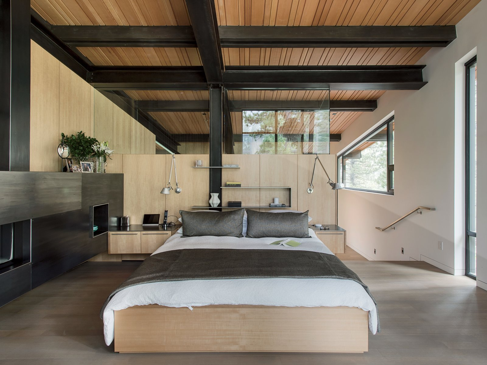 Hawkins created the built-in anigre bed and side tables in the master bedroom. Chenault designed the bedding; the sconces are from Artemide.  Bedrooms by Dwell from A Forest Sanctuary Designed to Support Autistic Triplets, Their Parents, and a Host of Caregivers