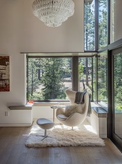 A Forest Sanctuary Designed to Support Autistic Triplets, Their Parents, and a Host of Caregivers - Photo 9 of 19 - In one corner of the room, an Arne Jacobsen Egg chair and ottoman rest on a flokati rug. Overhead is an Ecos pendant by Vistosi.