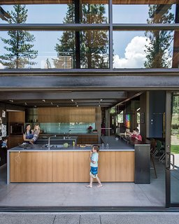 A Forest Sanctuary Designed to Support Autistic Triplets, Their Parents, and a Host of Caregivers - Photo 12 of 19 - The kitchen opens to the elements thanks to sliding doors from C.R. Laurence. The anigre in the kitchen is the same employed in the master bedroom.