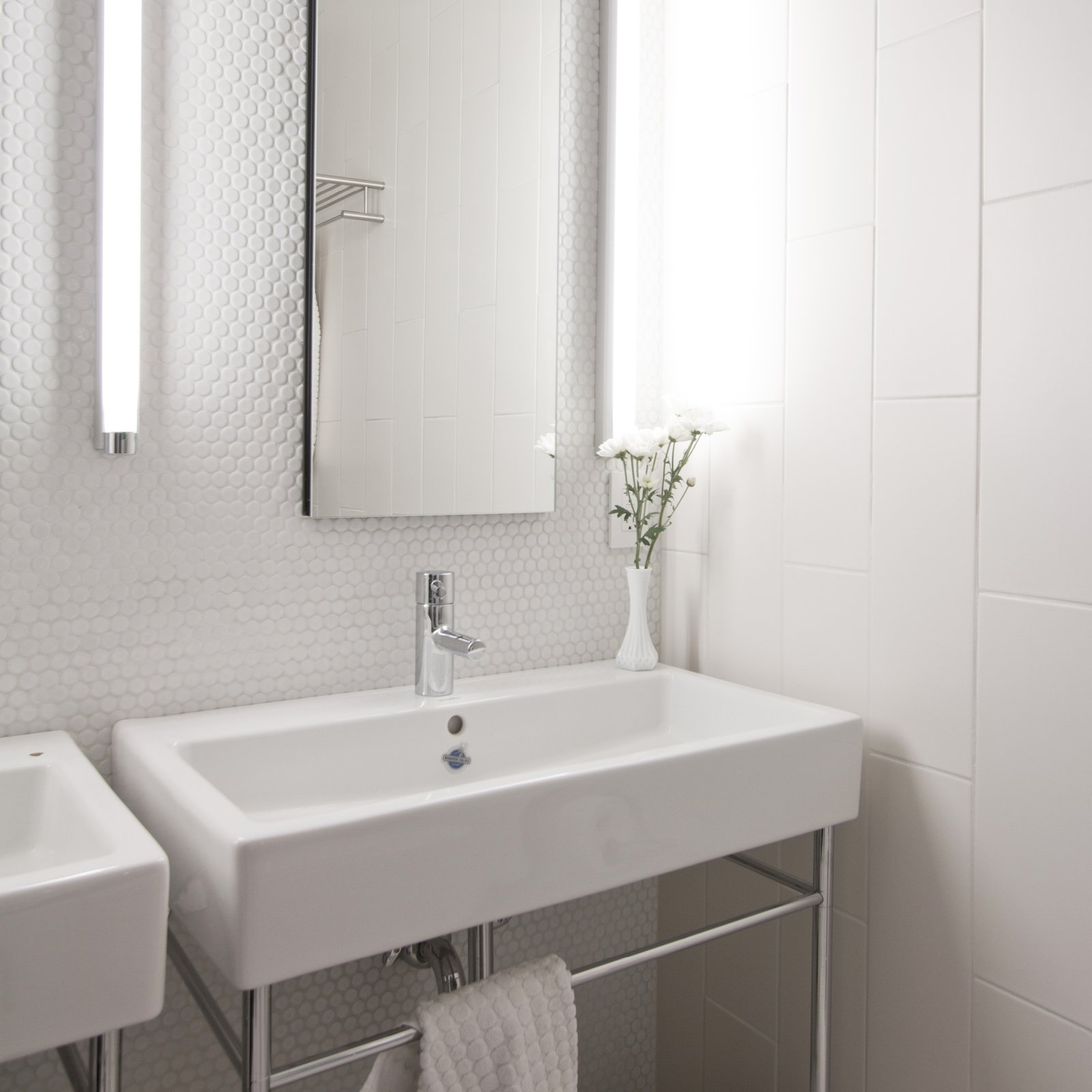 The main bathroom experiments with varying textured tiles, and is equipped with Duravit, American Stand, Toto and Kohler fixtures.