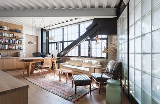5 Light-Filled Spaces That Use Glass Blocks Creatively - Photo 1 of 5 - Old concrete walls, multi-pane windows, and glass block walls hint at the previous life of this loft building as a garage. The glass block partition divides the living room from the bathroom and acts as a stylish buffer between the two spaces.