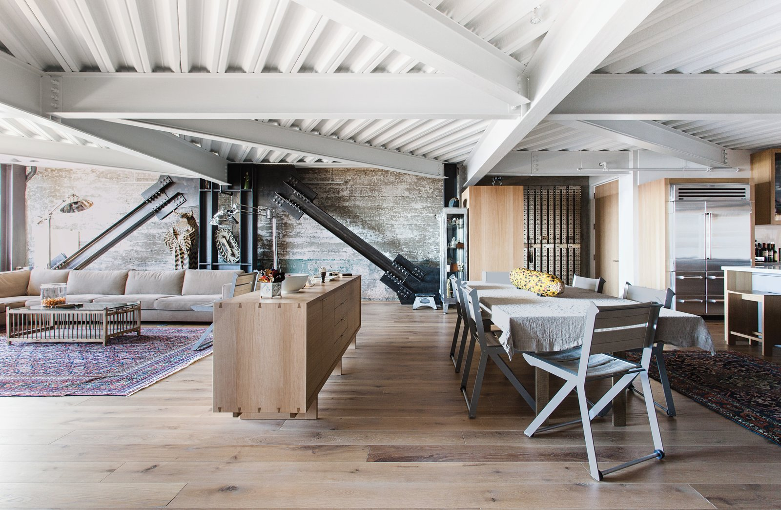 In the new 2,770-square-foot apartment, original I-beams brace the structure at dramatic angles and collide overhead, and the raw concrete is tempered by blackened steel, white-oak flooring, and bush-hammered Carrara marble—all selected by Willis.