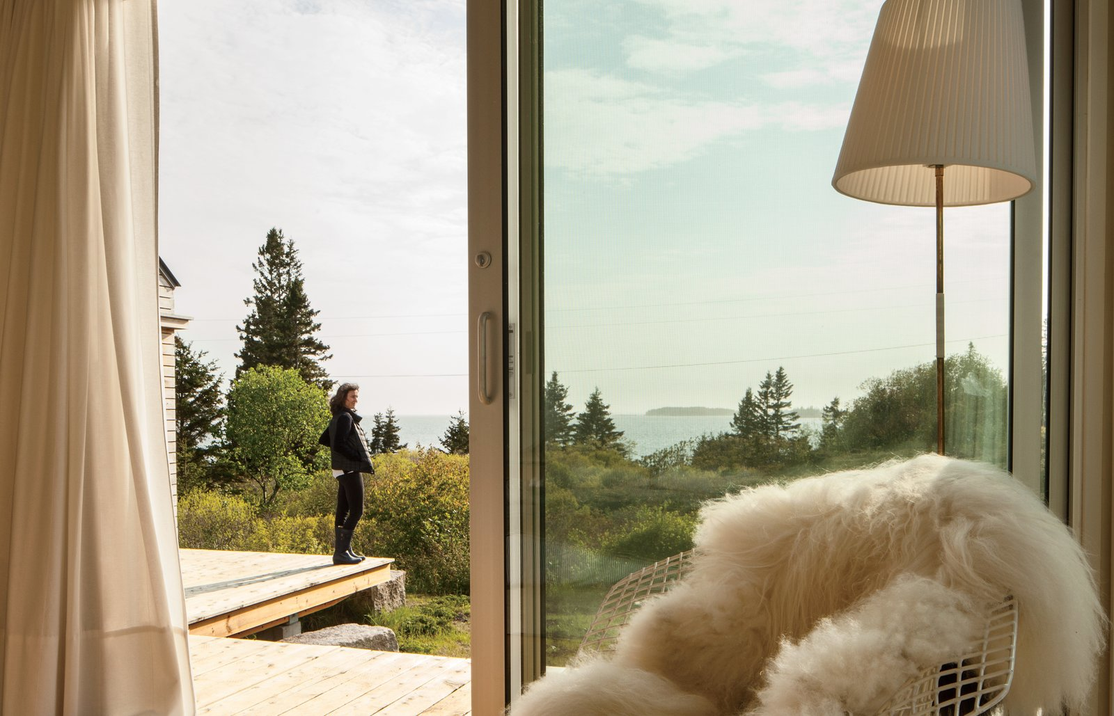 """Resident Nadja van Praag enjoys the view from the deck that connects the trio of structures. The idea for the deconstructed plan was inspired in part by Alvar Aalto sketches of a """"peeled apart"""" summer cabin, says architectural designer Riley Pratt, in which interconnected volumes surround a central courtyard. A Cluster of Cabins in a Former Quarry Makes a Simple Vacation Escape - Photo 5 of 13"""