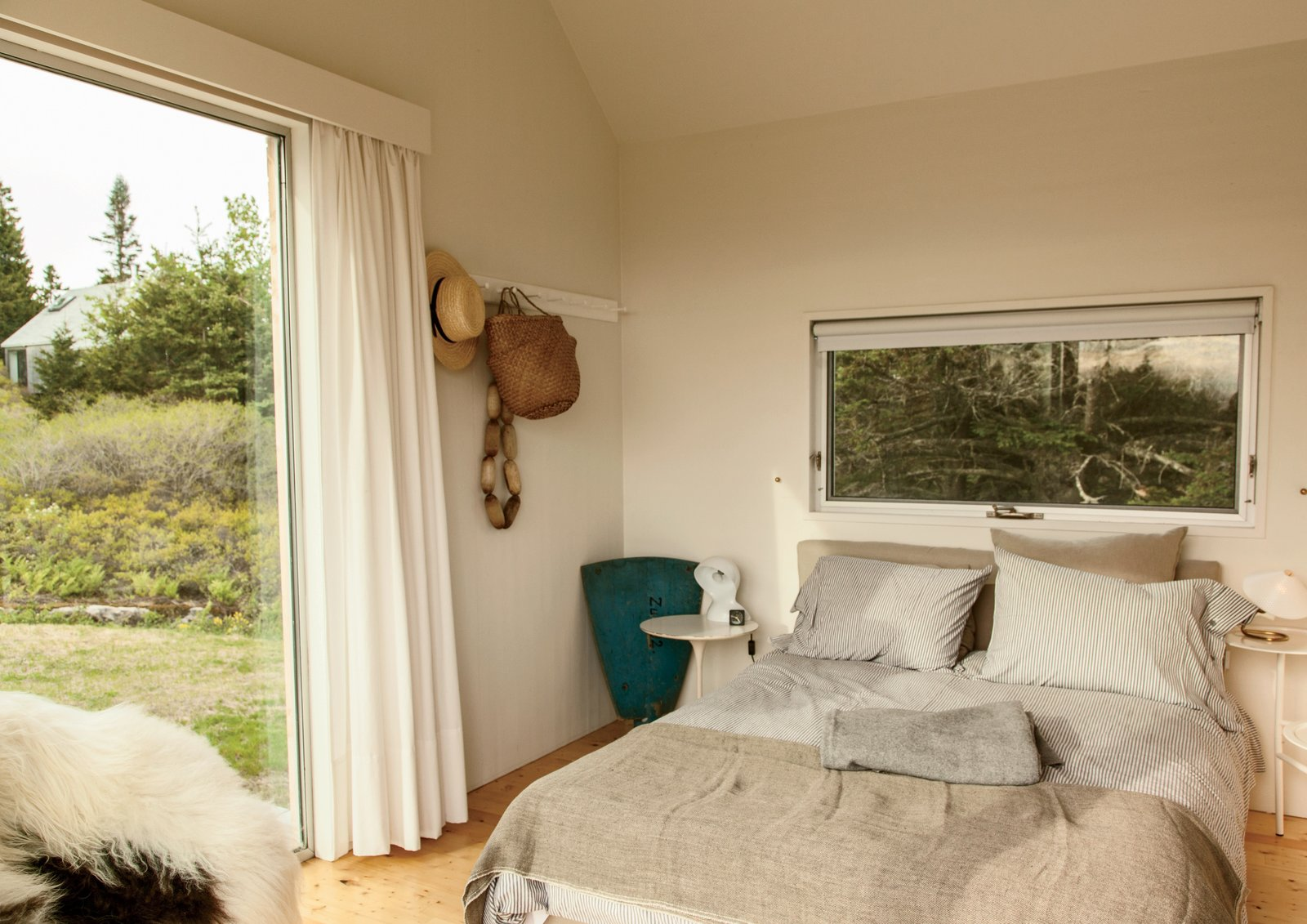 Situated between the main living space and the other bedroom, the middle cabin is furnished with a Calder side table by Konstantin Grcic, a vintage Dalu lamp by Vico Magistretti, and handwoven blankets from Swans Island Company.  Bedrooms by Dwell from A Cluster of Cabins in a Former Quarry Makes a Simple Vacation Escape