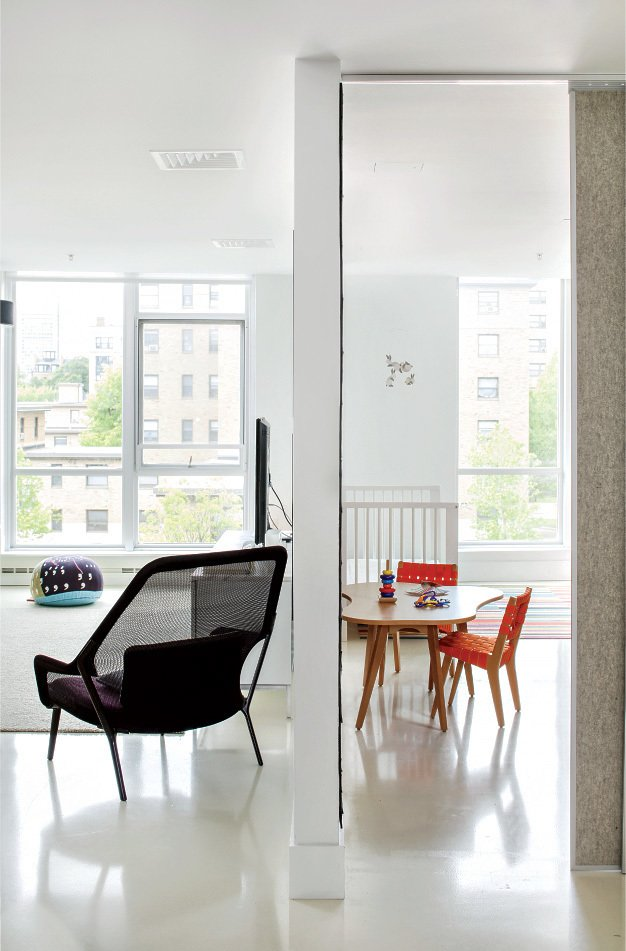 Felt-covered sliding doors made of acoustic substrate separate the children's room and living area. Tagged: Living Room and Chair.  Photo 7 of 8 in Boston Renovation Accents Minimalist White with Rich Felt Murals
