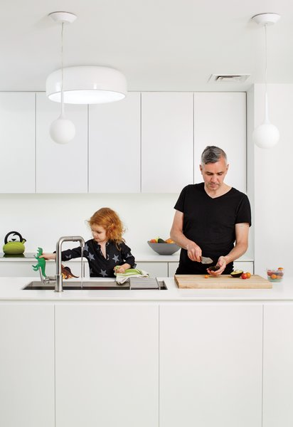 Brightening the kitchen was a renovation priority. The cabinets are custom, the sink is by Kohler, the ceiling lamp is Jasper Morrison's Smithfield C for Flos, and the Castore pendants are by Artemide.