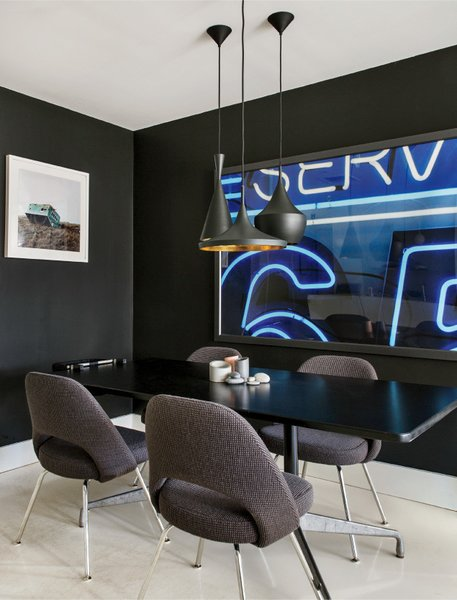 """In the dining area, a trio of Beat pendants by Tom Dixon hang over an Eames table for Herman Miller and Saarinen Executive Armless chairs from Knoll.  Flat Onyx Black paint by Glidden sets off a Corbin Smith photograph. """"It's like you're erasing things by painting,"""" Grimley says of the inky hue."""