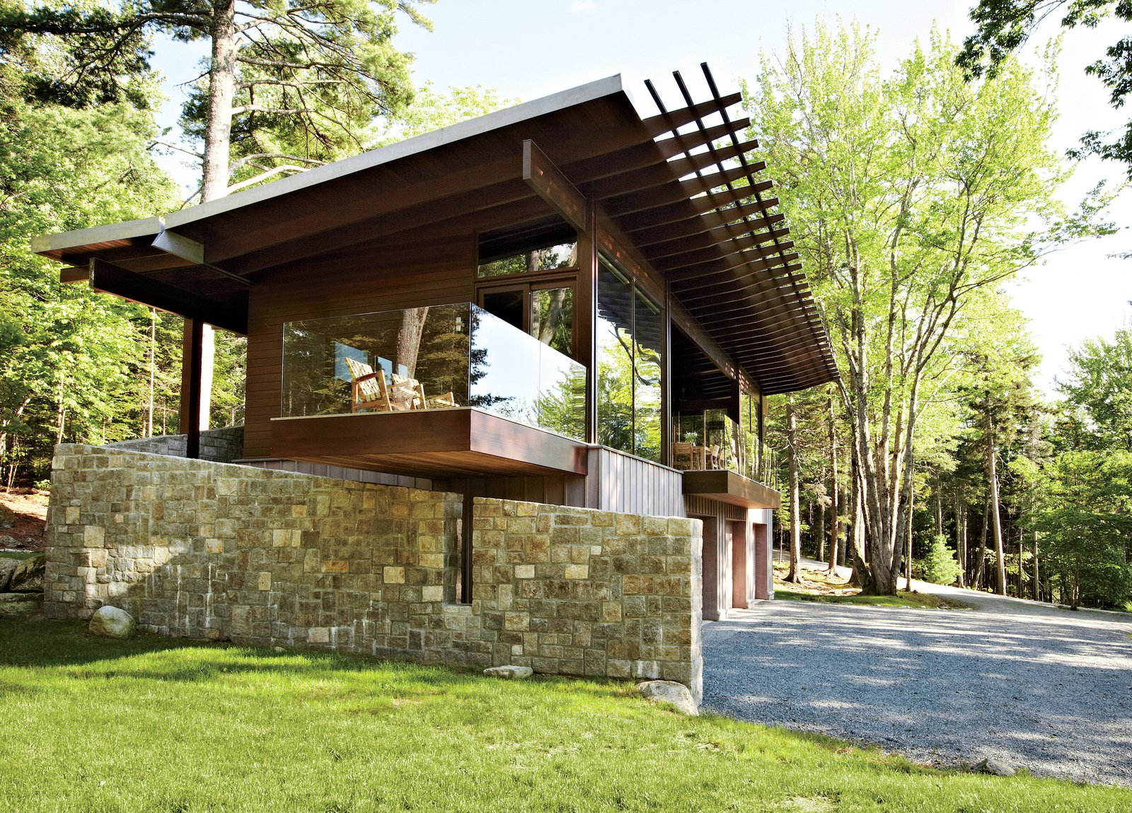 "From its locally quarried stone foundation to its zinc-coated copper roof, the cottage was inspired by its surroundings. ""We talked a lot with our client about what the materiality would be,"" says architect Karen Stonely, who, citing the organic style of Bar Harbor architect Robert Patterson, designed the structure with wood rather than drywall. Tagged: Exterior, Metal Roof Material, House, and Wood Siding Material.  Photo 1 of 5 in Frank Lloyd Wright-Inspired Style and Camping Collide in Maine"