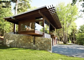 "Frank Lloyd Wright-Inspired Style and Camping Collide in Maine - Photo 1 of 5 - From its locally quarried stone foundation to its zinc-coated copper roof, the cottage was inspired by its surroundings. ""We talked a lot with our client about what the materiality would be,"" says architect Karen Stonely, who, citing the organic style of Bar Harbor architect Robert Patterson, designed the structure with wood rather than drywall."