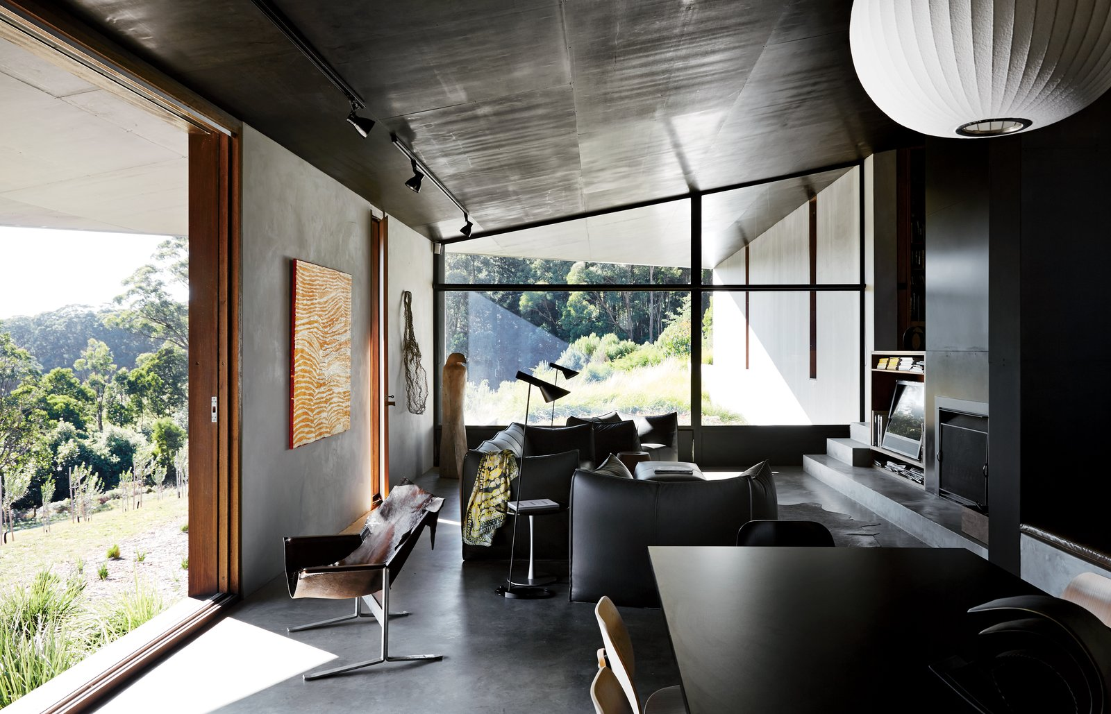 The interior shares the structure's attention to texture and line. Furnishings include a pair of Arne Jacobsen's AJ floor lamps and a Le Bambole sofa, armchairs, and ottoman by Mario Bellini for B&B Italia. Tagged: Living Room, Chair, Sofa, Lamps, Pendant Lighting, Floor Lighting, and Ceiling Lighting.  Photo 9 of 10 in Richly Furnished Home Frames Striking Landscape Views