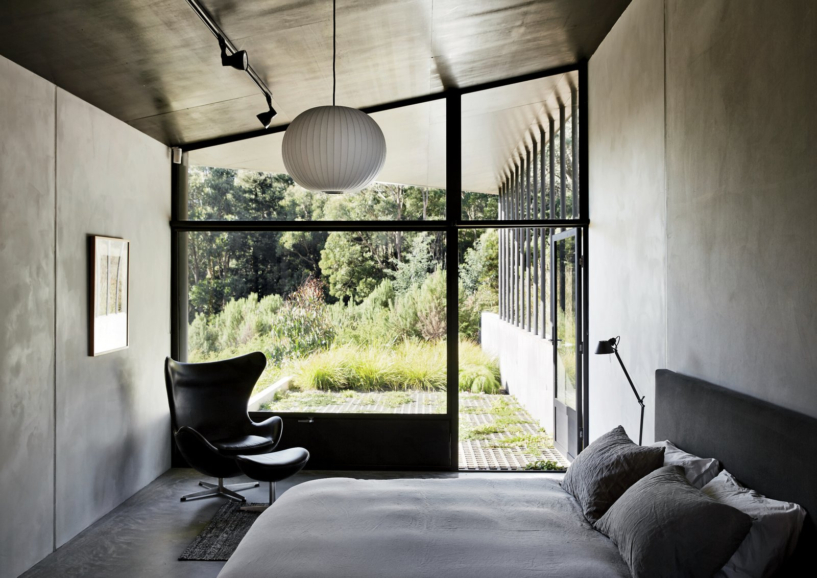 The master bedroom, which features a bed by Paolo Piva, an Egg chair by Arne Jacobsen, and a Ball pendant lamp by George Nelson, opens directly onto a verdant patio. The metal shutters at the bottom of the window keep out flying embers in case of fire. Tagged: Bedroom, Lamps, Bed, Chair, Table Lighting, Ceiling Lighting, and Pendant Lighting.  Photo 6 of 10 in Richly Furnished Home Frames Striking Landscape Views