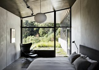 Richly Furnished Home Frames Striking Landscape Views - Photo 6 of 10 - The master bedroom, which features a bed by Paolo Piva, an Egg chair by Arne Jacobsen, and a Ball pendant lamp by George Nelson, opens directly onto a verdant patio. The metal shutters at the bottom of the window keep out flying embers in case of fire.