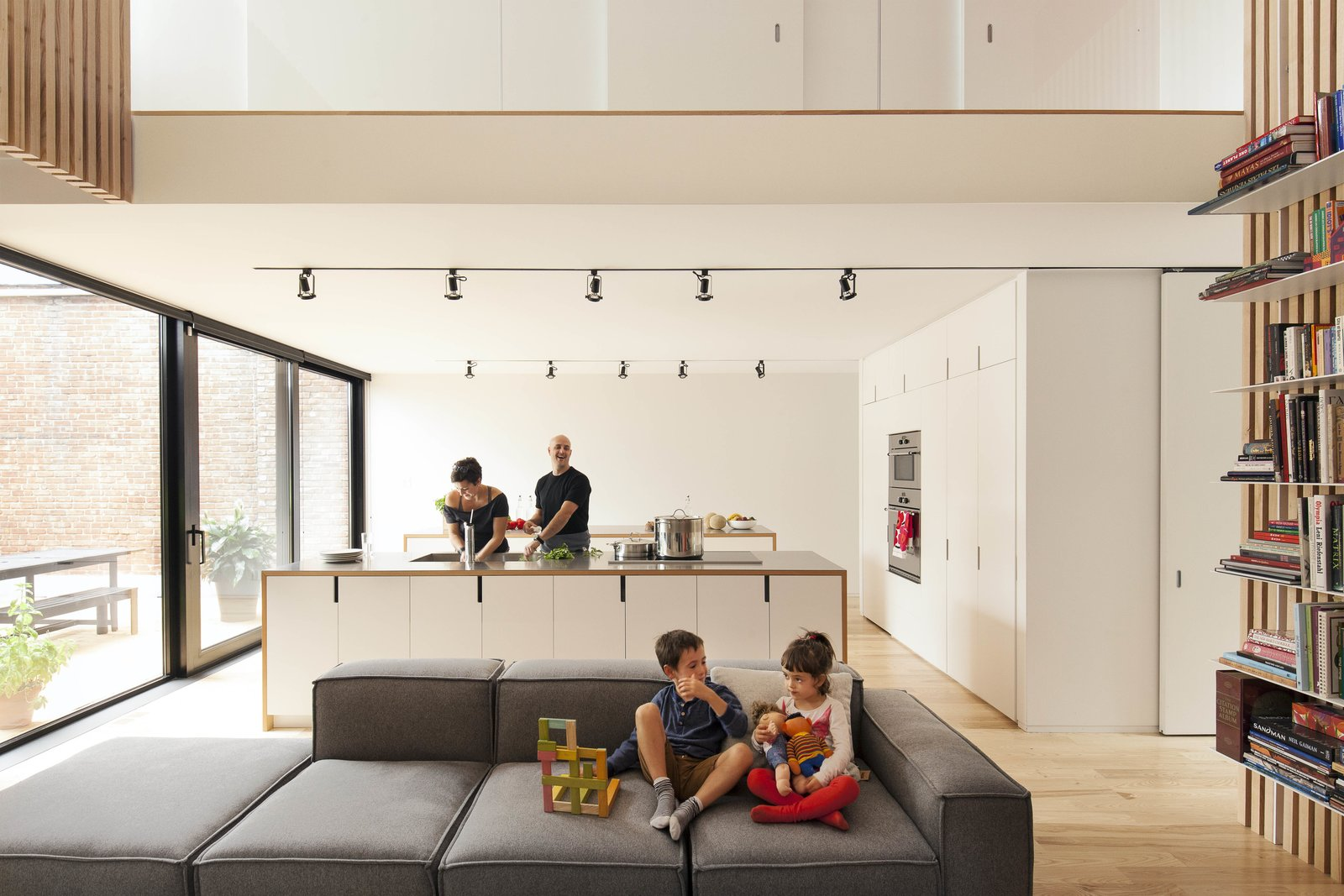 "The architects arranged the ""service areas"" of the home—closets, a bathroom, storage space, and most of the kitchen appliances—in a block near the entrance, a move that allows for clear views across the open-plan kitchen and living areas."