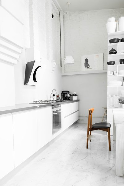 "In the kitchen, an exposed brick wall stands out against the milky smoothness of the marble tile floors. ""I wanted the house to be raw and interesting,"" Kolasiński explains. The large cupboard was designed by his company. Appliances are by Smeg and the stove hood is by Elica."