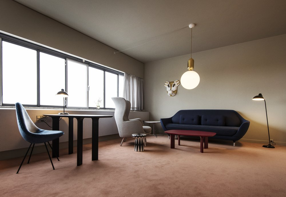 """""""I designed the room the same way I think about my own house,"""" Hayon says. """"I wanted a nice place to read, a lovely desk to write on, and a sofa for relaxing or conversation—plus some beautiful accessories and plants."""" The seating area features a Favn sofa, Ro armchair, Analog desk and coffee table, Kaiser Idell floor and table lamp, all by Fritz Hansen. The Aballs pendant light is by Parachilna and the side table is by Bosa."""