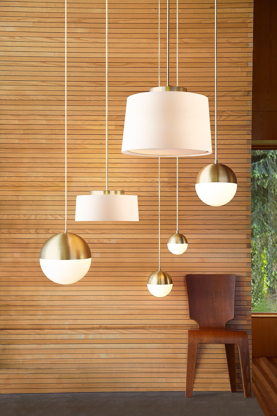 The collection combines influences from modernism and the Arts and Crafts movement. The Cedar & Moss pendants with a brushed satin finish are shown here.