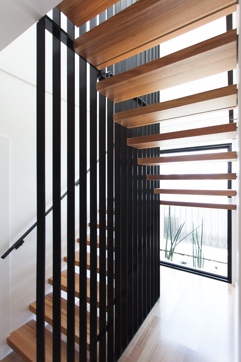 A striking stair defines the entry to the house; it features minimalist floating timber stair treads wrapped around a woven steel mesh blade wall. Tagged: Staircase, Metal Railing, and Wood Tread.  190+ Best Modern Staircase Ideas by Dwell from Make an Appearance Like These 9 Modern Entryways