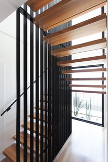 A Modular Beach Home in Australia Allows One Family to Keep an Eye on the Surf - Photo 6 of 8 - A striking stair defines the entry to the house; it features minimalist floating timber stair treads wrapped around a woven steel mesh blade wall.