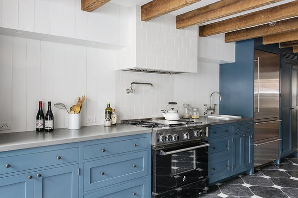 """They knew they wanted a big kitchen where all of their friends could stand around and be involved in the cooking process,"" Roberts said of the owners. Exposed beams stripe a ceiling above Wood Mode cabinets painted Newport Green by Benjamin Moore."