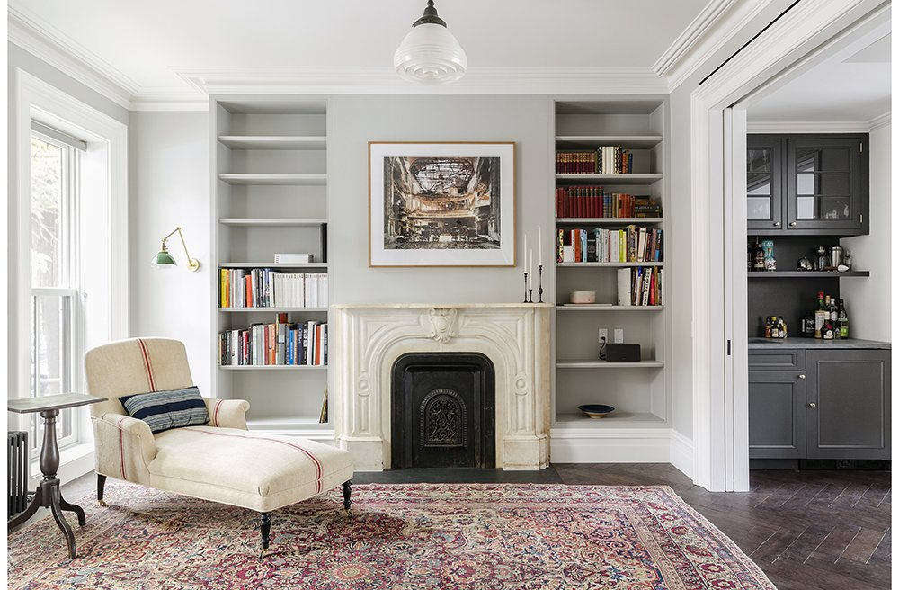 As much as the owners and Roberts wanted – and needed – to modernize the home, they also tried to honor some of its historical touches. They preserved the mantel, and replaced the plaster crowns on the parlor level. The antique chaise is by Lisa Sherman, and the walls are painted pavilion gray by Farrow & Ball.  Photo 3 of 8 in A Neglected Brooklyn Townhouse Becomes a Home That's Primed for Entertaining