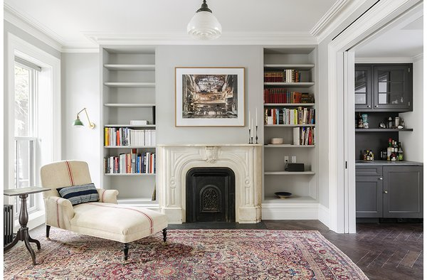 As much as the owners and Roberts wanted – and needed – to modernize the home, they also tried to honor some of its historical touches. They preserved the mantel, and replaced the plaster crowns on the parlor level. The antique chaise is by Lisa Sherman, and the walls are painted pavilion gray by Farrow & Ball.