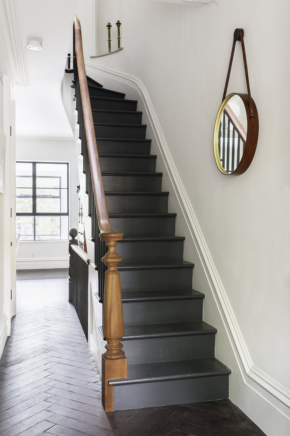 Reclaimed oak with a custom finish by LV Wood surrounds a staircase in a herringbone pattern. The new stairs are painted off black by Farrow & Ball, and the handrail that lines them is of salvaged mahogany.  190+ Best Modern Staircase Ideas by Dwell from A Neglected Brooklyn Townhouse Becomes a Home That's Primed for Entertaining
