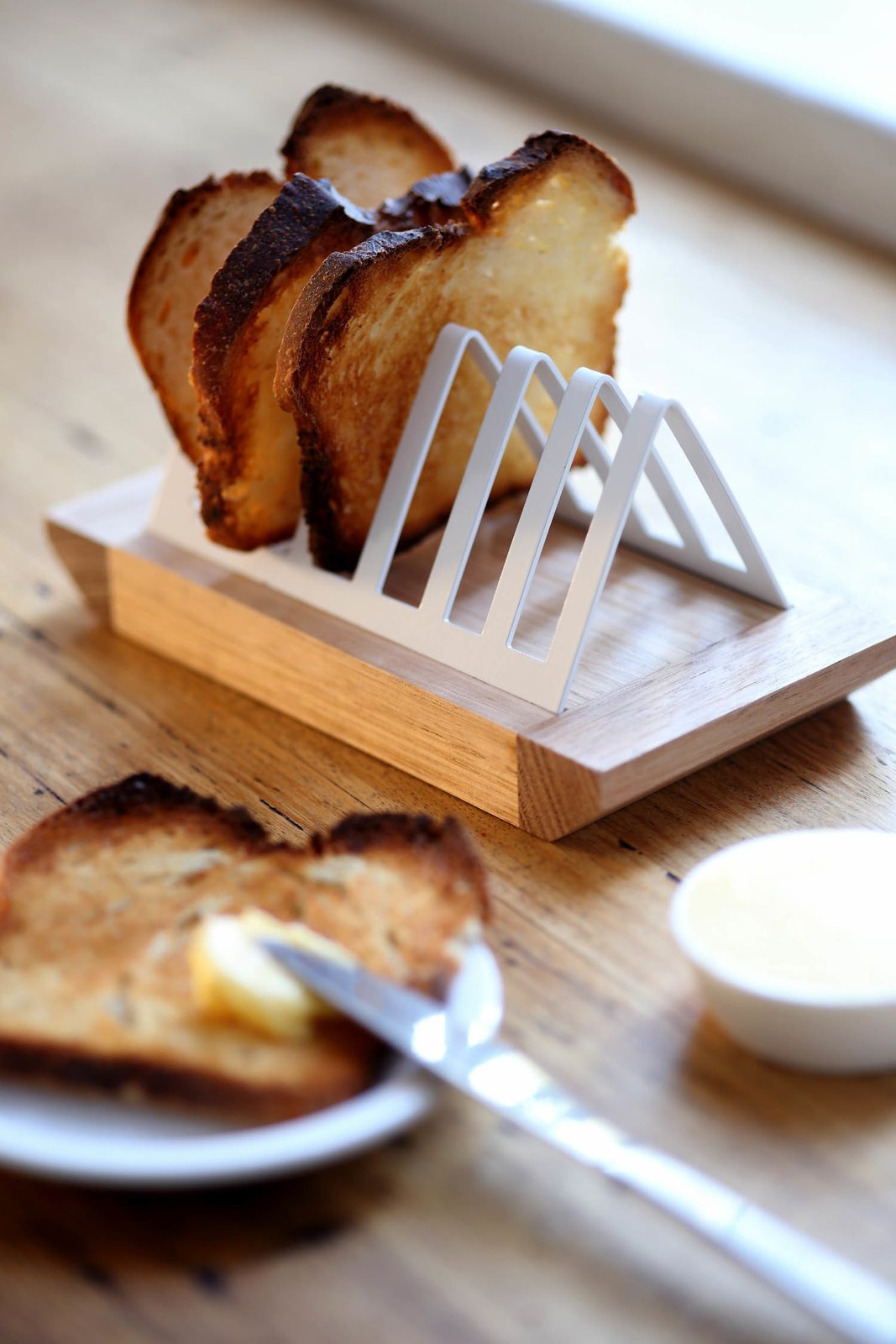 """""""We find ourselves in the marginal group who still love a simple slice of toast and decided to design something to emphasize this as well as solve a problem that hasn't been addressed for a good 20 to 30 years,"""" Pedersen says of this toast rack. """"The size and shape of bread has changed, and so we found that our old inherited toast racks didn't work anymore! Our solution is a simple combination of a wooden breadboard base with a steel or brass rack, which clips in nicely and holds toast [slices] of varying thickness.""""  Photo 5 of 16 in Two Cool Surfers Design Some Serious Furniture"""