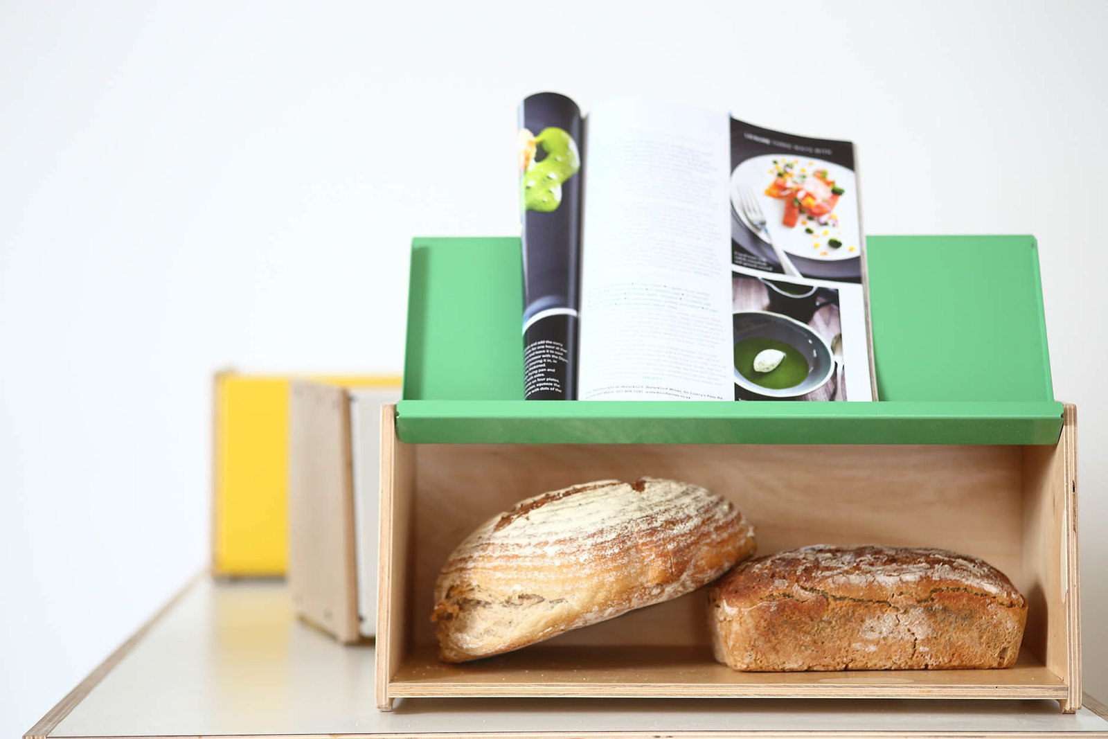 """""""This piece came out of a need for a bread bin which carried our aesthetic into the kitchen space,"""" Pedersen says. """"Kitchens have become increasingly smaller; we are aware that it's precious real estate, hence the more compact size and the added feature of the lid flipping over to become a recipe book stand."""" Two Cool Surfers Design Some Serious Furniture - Photo 6 of 16"""