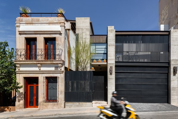 """The early-20th-century structure is seen next to the 300 square meter modern addition. A garage and patio were added, as well as a balcony that would complement the proportions of those in the original building. According to Quevedo, the biggest challenge was to approach both structures with a """"common language"""" and explore the idea that """"preservation and modernity can coexist."""" Photo  of Hybrid Home modern home"""