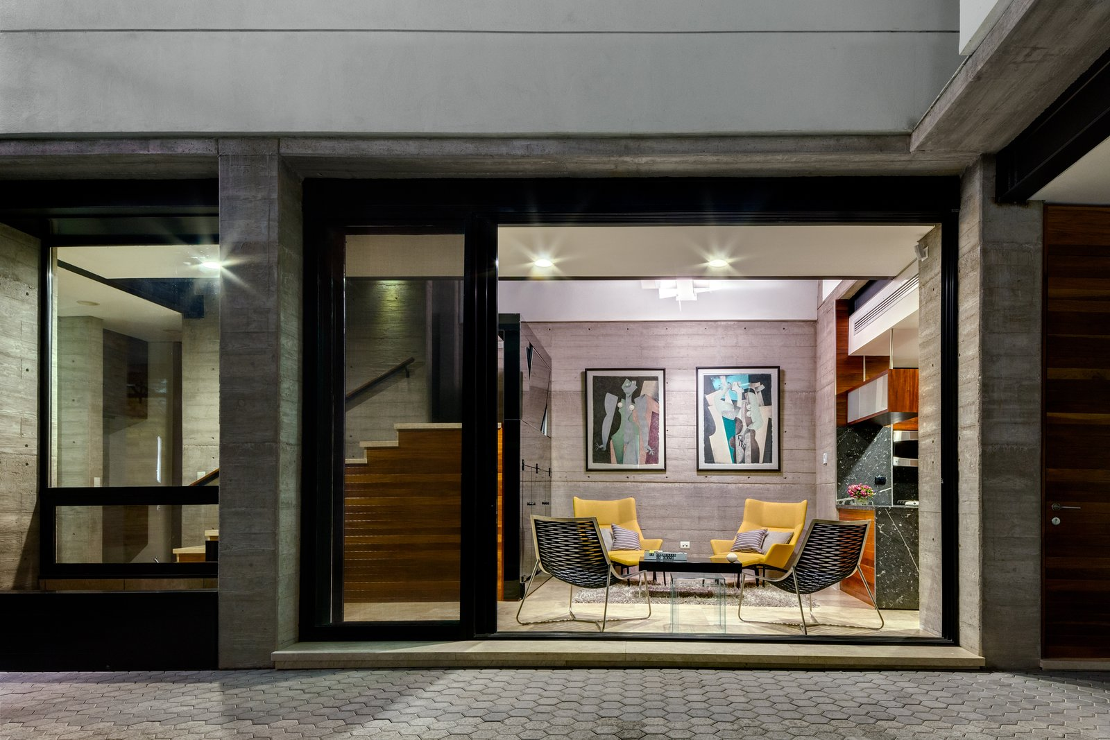 The home's living room connects to the patio through sliding glass doors. Both social spaces, the living room and kitchen, have double high ceilings. These areas are divided by the granite kitchen bar, and are unified by the open patio.  Hybrid Home by Sarah Akkoush