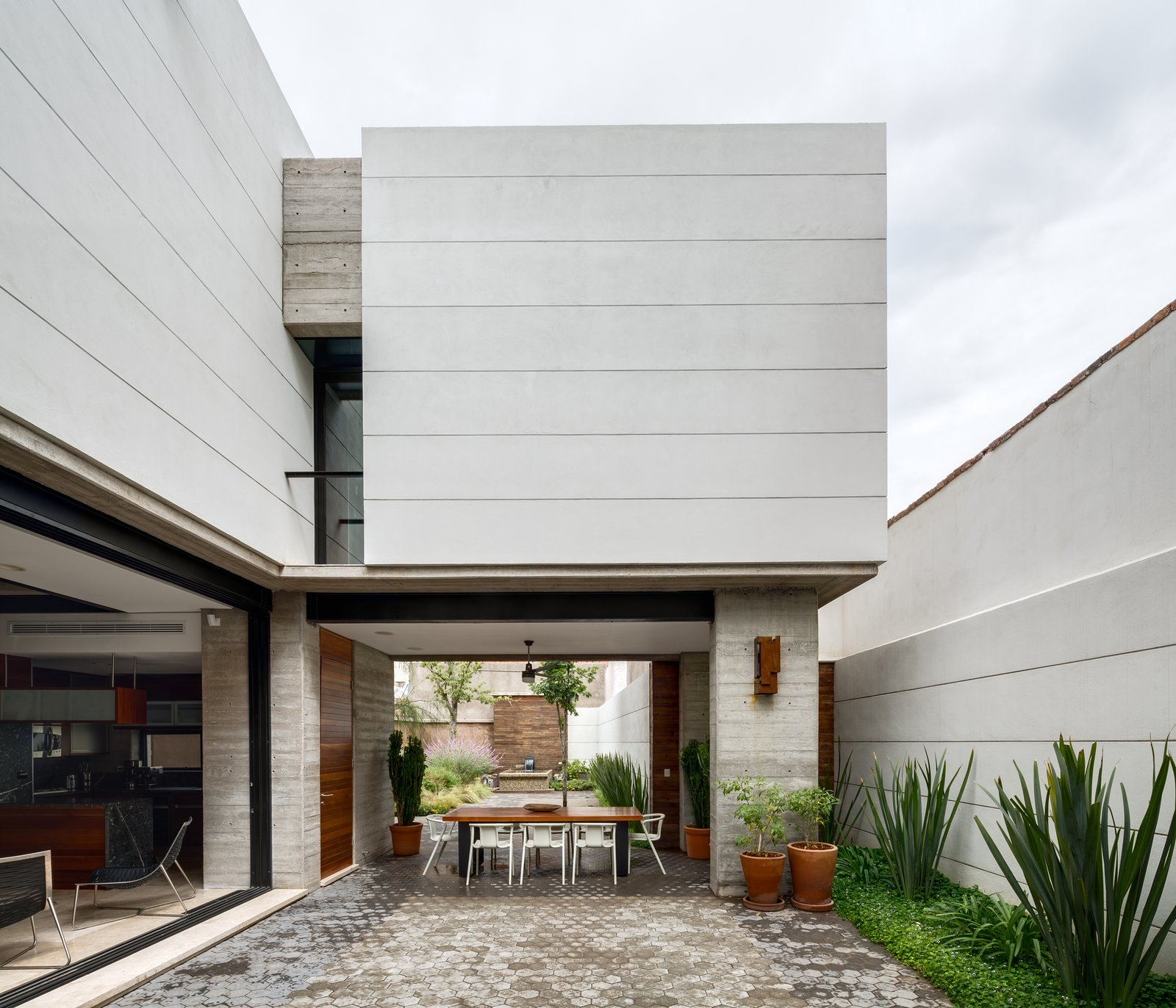 The open and airy courtyard and dining area encourages outdoor living. A custom table made from Andiroba wood and Magis White Air armchairs complete the space.