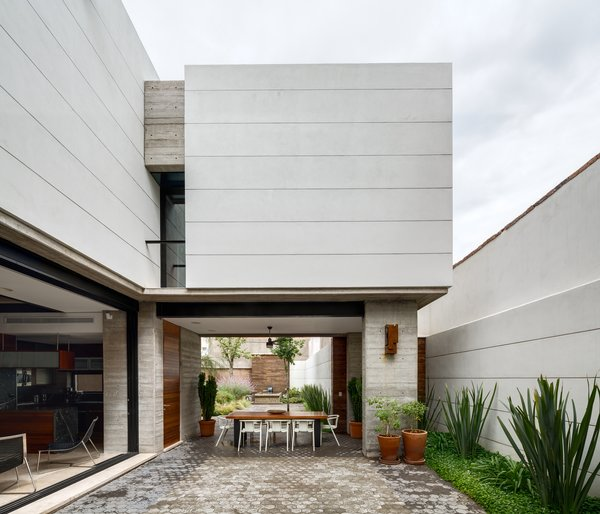 The open and airy courtyard and dining area encourages outdoor living. A custom table made from Andiroba wood and Magis White Air armchairs complete the space. Photo 4 of Hybrid Home modern home