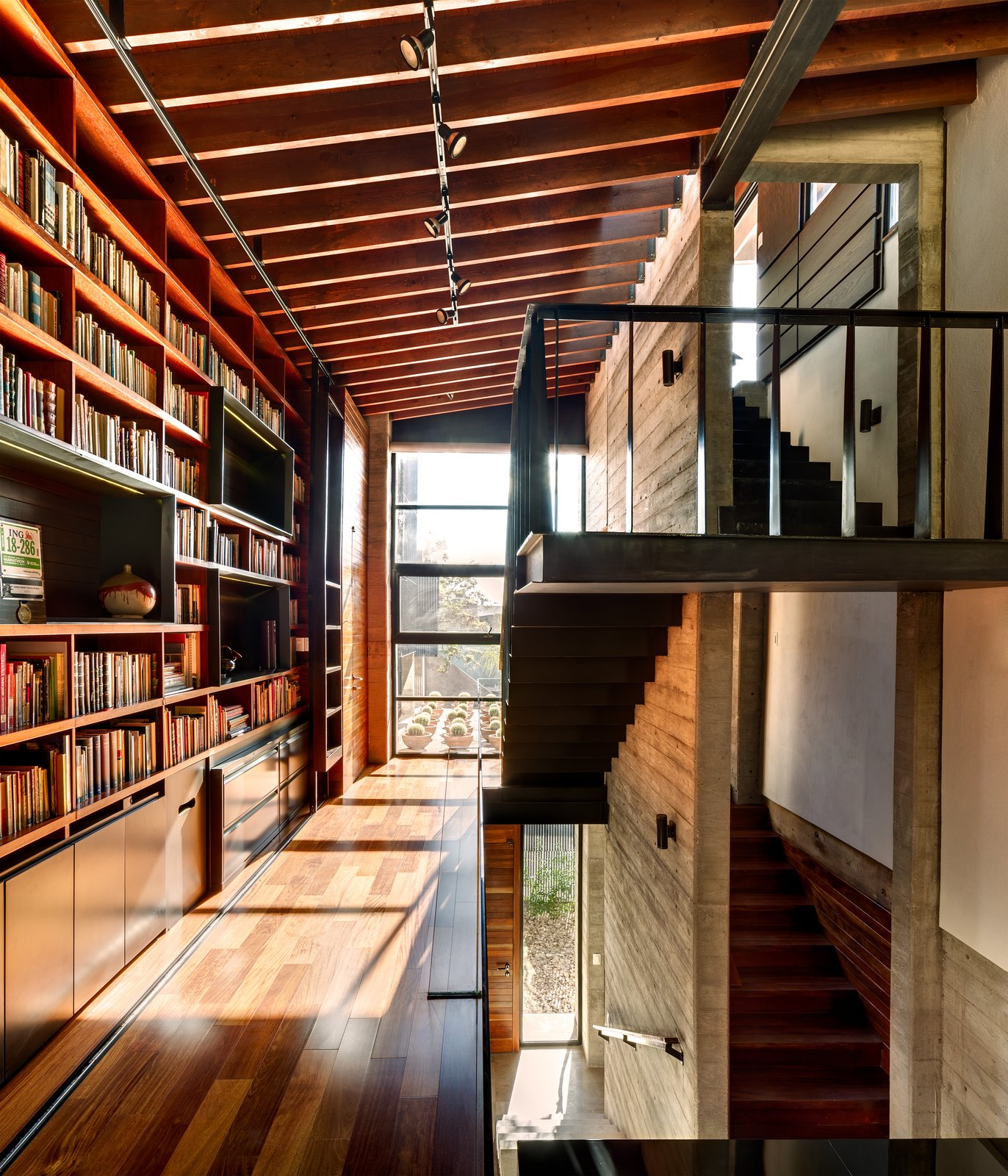 Suspended over the living room, the library bridge connects the second floor rooms of the house. The transitional space contains built-ins and desks where the owners and their three-year-old daughter can sit and read. The steel of the staircase is supported entirely by the adjacent concrete wall. A marriage of concrete, wood, and glass is used in the space, and the large windows let light in and offer a view of the roof garden.