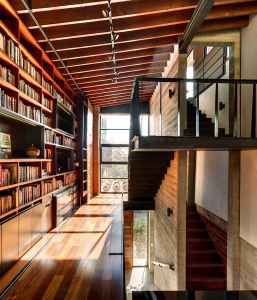 Suspended over the living room, the library bridge connects the second floor rooms of the house. The transitional space contains built-ins and desks where the owners and their three-year-old daughter can sit and read. The steel of the staircase is supported entirely by the adjacent concrete wall. A marriage of concrete, wood, and glass is used in the space, and the large windows let light in and offer a view of the roof garden. Photo 8 of Hybrid Home modern home