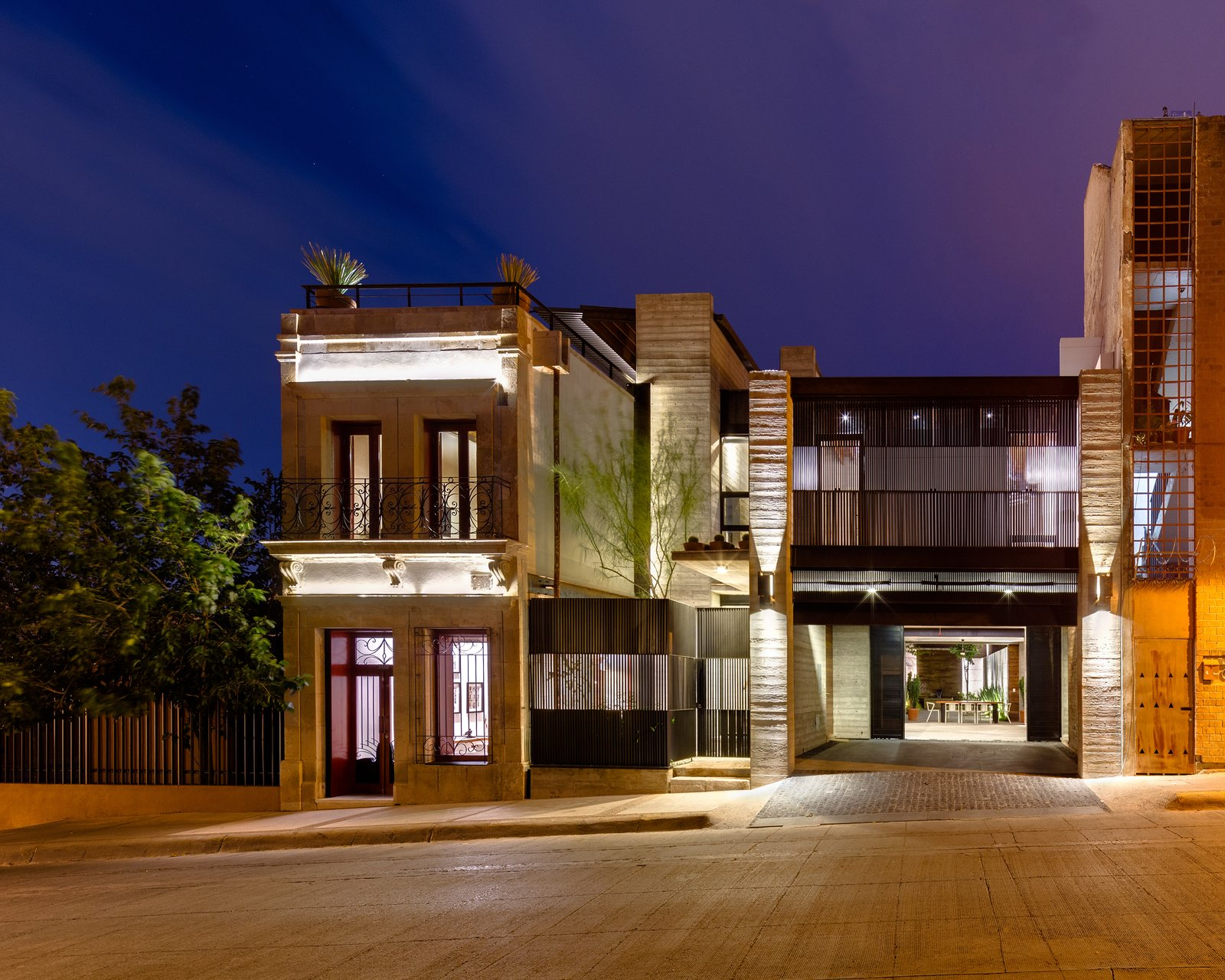 The front elevation is seen at night. The old structure fits on a compact 130-square-foot lot, while the new building adds an extra 1,000 square feet. Adobe walls, wood beams, limestone facade, and earthen roof all make up the tactful blend of old and new.