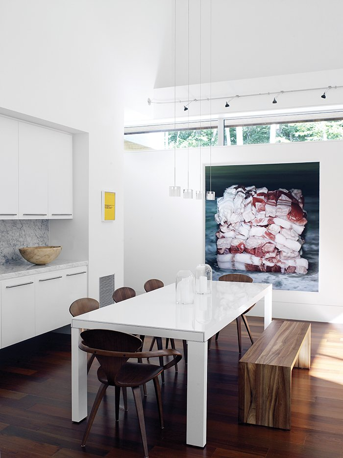 A white lacquer Ligne Roset dining table is joined by a wood bench from Room & Board and bent-plywood Cherner chairs. Baconcube 4 by Cindy Wright hangs on the wall. Tagged: Dining Room, Table, Chair, Medium Hardwood Floor, and Pendant Lighting.  Photo 3 of 12 in Art-Filled Hamptons Vacation Home