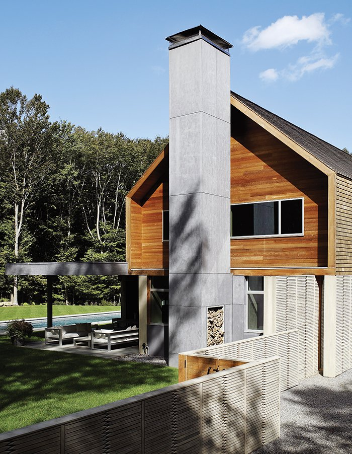 The gabled house, constructed from precast concrete panels by Superior Walls with wood framing, offers a pared-down suggestion of a traditional New England silhouette. The exterior cedar paneling also appears on the ceiling of the custom-built chef's kitchen inside.