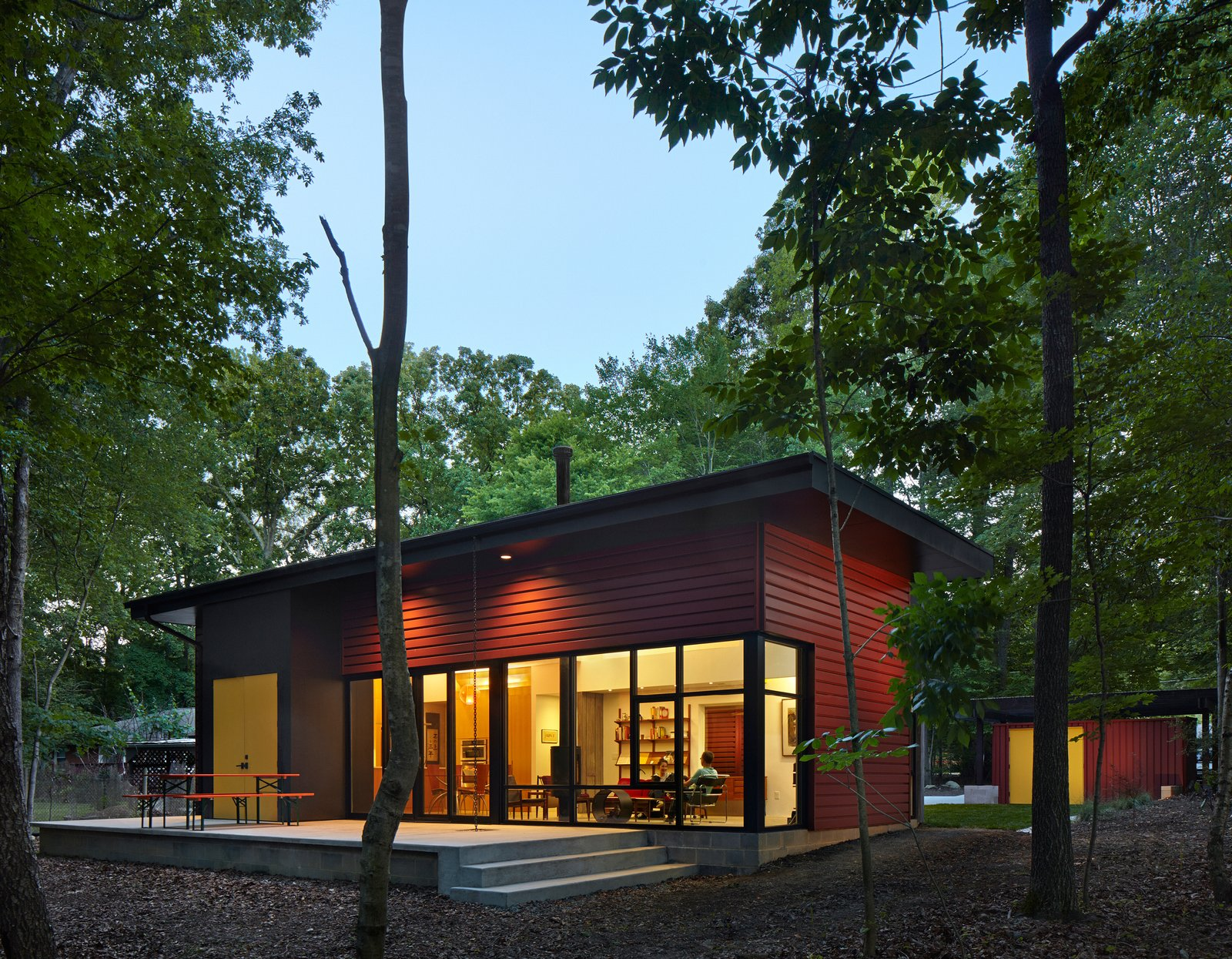 """Nestled in a forest, the residence consists of three volumes. The patio, enhanced by a German-made beer garden table, is an extension of the living room floor, creating an indoor-outdoor living space. """"It's one way a small space can be made to feel larger,"""" says architect Jason W. Hart. All of the exterior doors are painted marigold, providing a friendly pop of color. Tagged: Exterior, Metal Siding Material, and House.  Tiny Homes by Scott Saunders from This Light-Filled Metallic Home Embraces Its Wooded Site"""