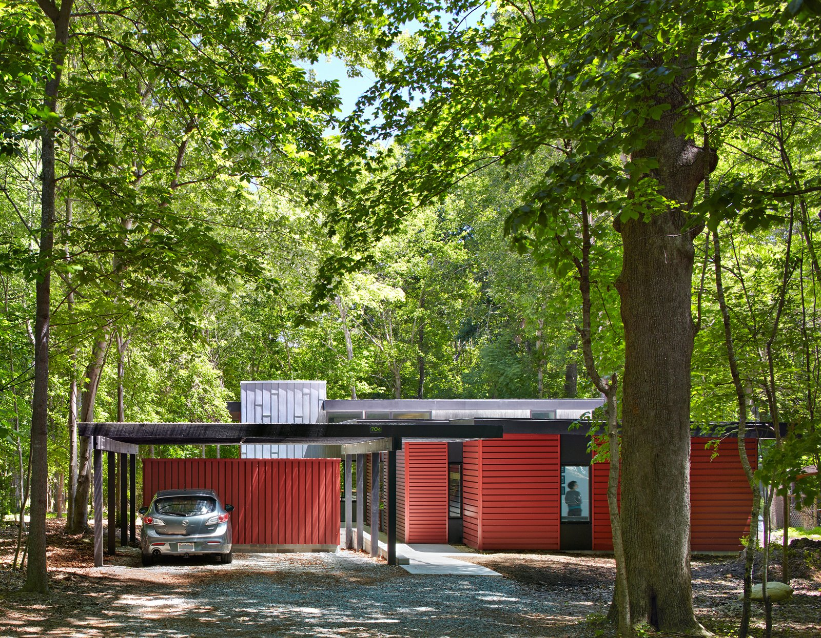 "Topped with translucent polycarbonate roof panels, the carport and storage shed helps buffer the home from the road. ""It's part of easing into the site with increasing enclosure along the entry axis,"" Hart says. ""We created a purposefully drawn-out experience that's intended to heighten awareness of the site and gradually transition from the forest to the home."" Tagged: Exterior, House, and Metal Siding Material.  Tiny Homes by Scott Saunders from This Light-Filled Metallic Home Embraces Its Wooded Site"